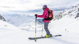Skifahrer in roter Jacke macht Pause und schaut auf die Alpen bei St. Anton in Vorarlberg