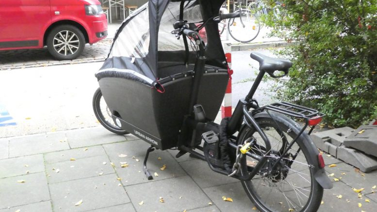 schwarze Lastenbike mit Windschutz aus PVC-Klarsicht