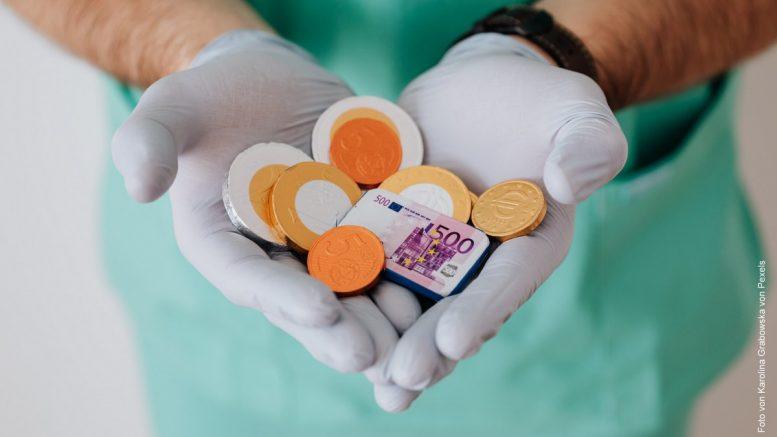 Arzt im grünen Kittel mit weißen Einweghandschuhen hält Geld