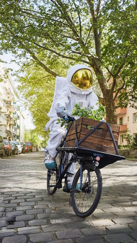 Astronaut in der Stadt auf dem Fahrrad