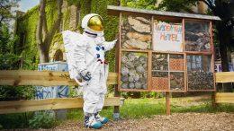 Astronaut vor einem Insektenhotel