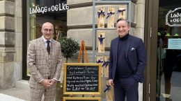 Zwei Männer am Werbeschild vor dem GEschäft von Ladage & Oelke