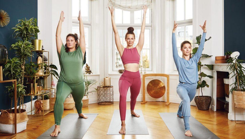 Drei Frauen tragen beim Yoga chakrana