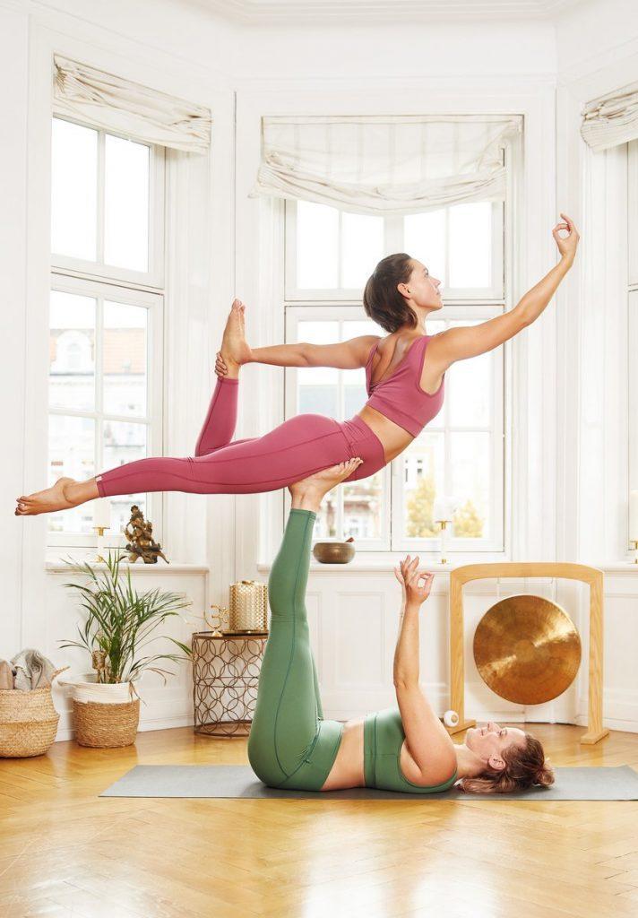 Frau balanciert auf einer anderen Frau beim Yogy