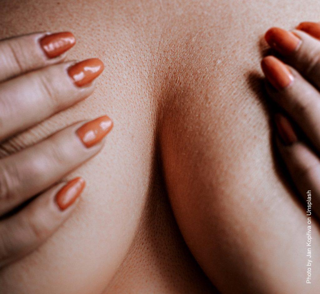 Eine Frau bedeckt ihre Brust mit ihren Händen