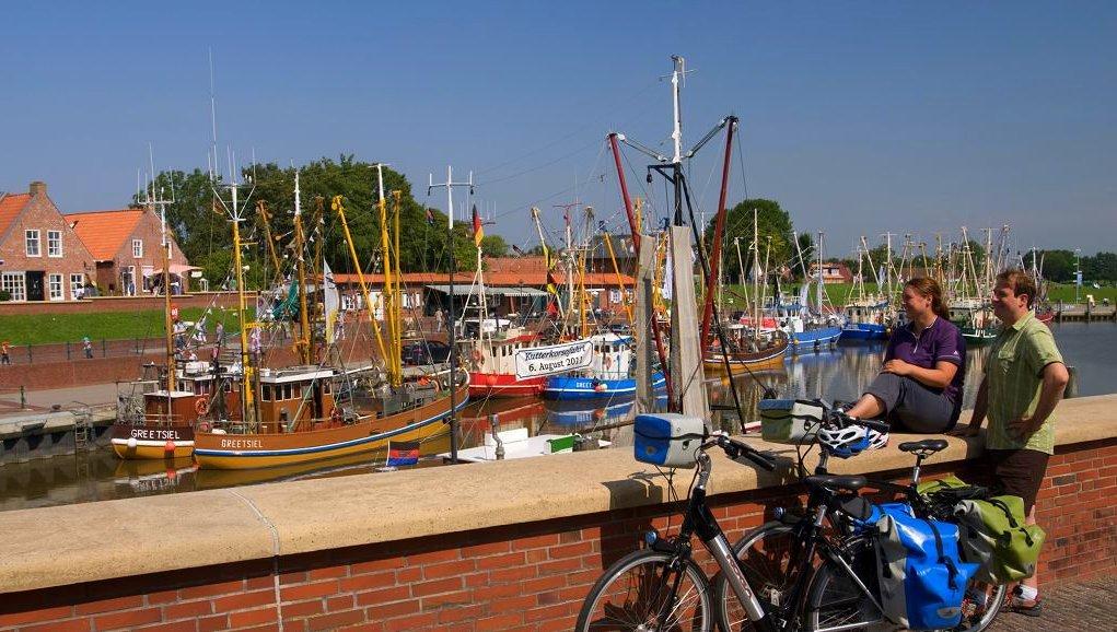 Fahrradfahrer machen Pause am Greetsieler Hafen