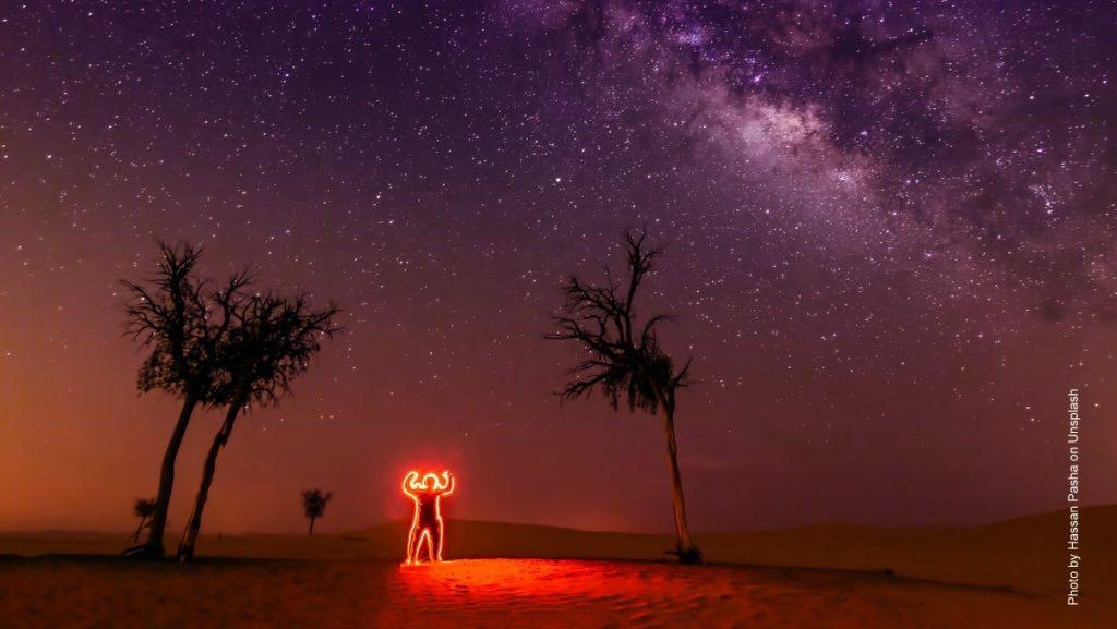 Kunstinstallation roter Neonmann in der Wüste von Abu Dhabi