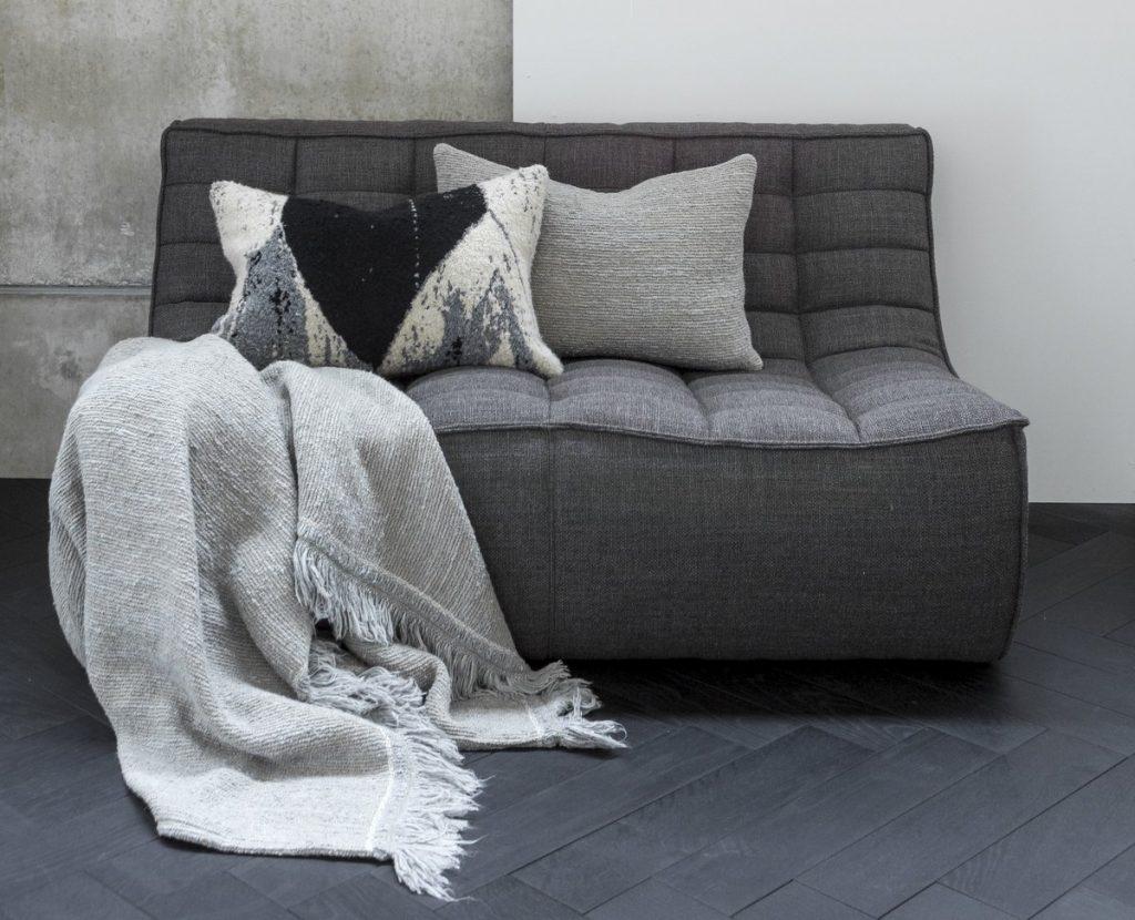 graues modernes Sofa mit Decke und Kissen