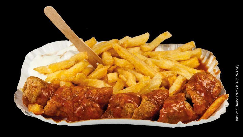 Currywurst auf Pappteller mit Pommes Frites