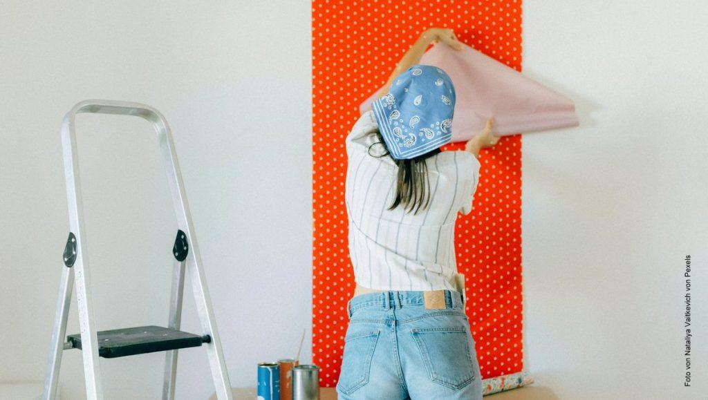Eine junge Frau tapeziert eine Wand mit einer rot weißen Tapete mit Polka Dots