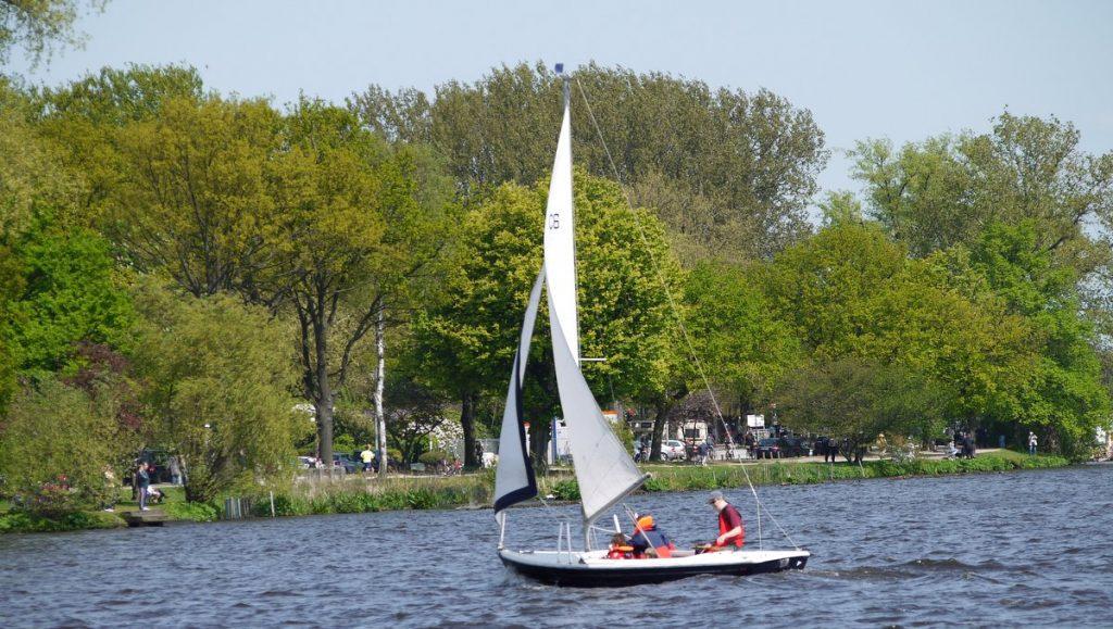 Segelboot auf der Außenalster mit Spazierweg