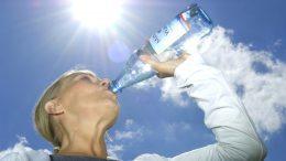 Frau trinkt aus Mineralwasserflasche