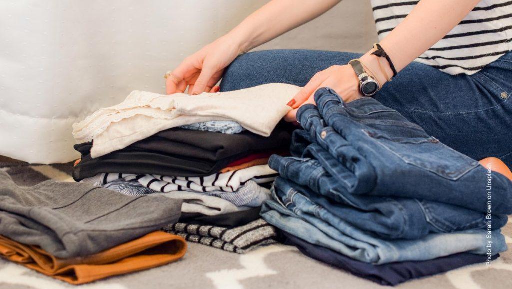 Frau sortiert Kleidung und räumt auf