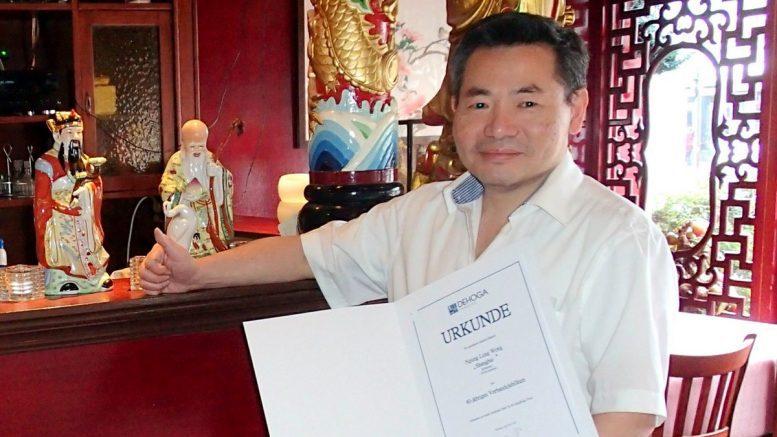 Restaurantinhaber Chi Sing Wong vom Restaurant Shanghai in Fuhlsbüttel mit Ehrenurkunde