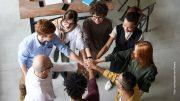 Ein Team Meeting alle legen die Hände aufeinander