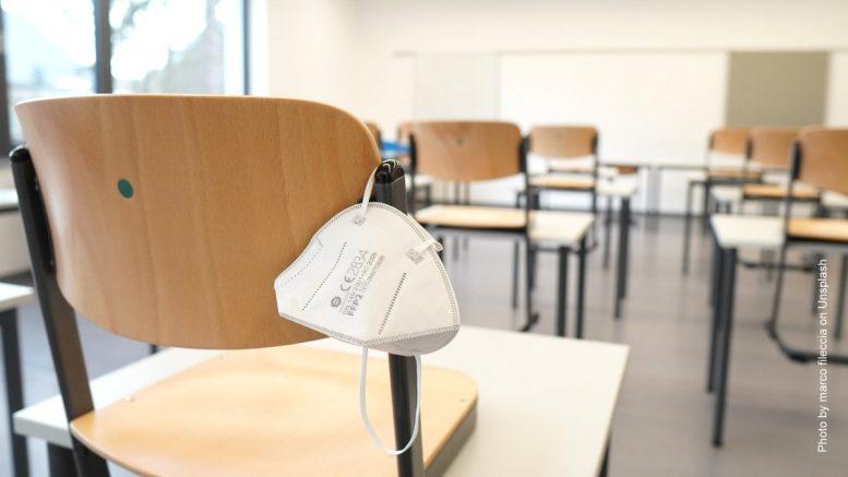 FFP2 Maske hängt an einem Stuhl