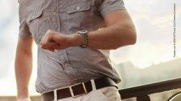 Mann im Kurzarmhemd schaut auf die Uhr