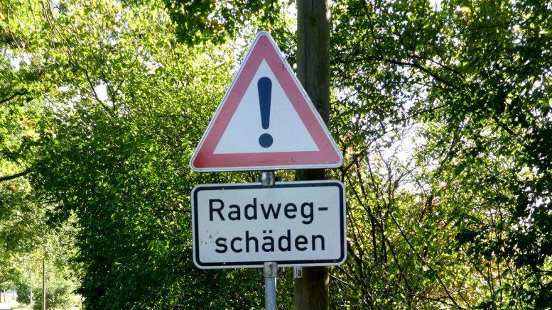 Straßenschild weißt auf Radwegschäden hin
