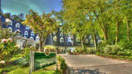 Das Hotel und Restaurant Waldhaus in Reinbek, Blick auf das Hotel unter Bäumen