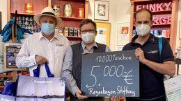Symbolische Scheckübergabe, drei Männer mit Gesichtsmasken