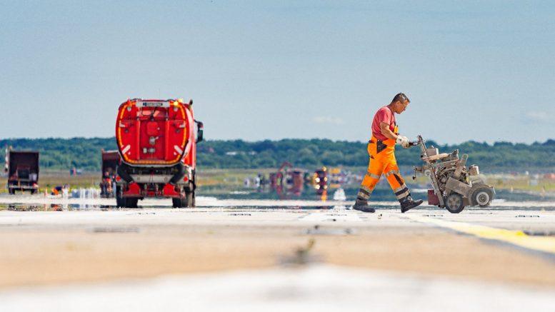Arbeiter bringt Markierungen auf der Start- und Landebahn des Hamburger Flughafens an