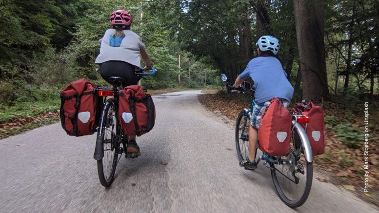 Mutter mit Kind fahren auf einer Radtour durch einen Wald