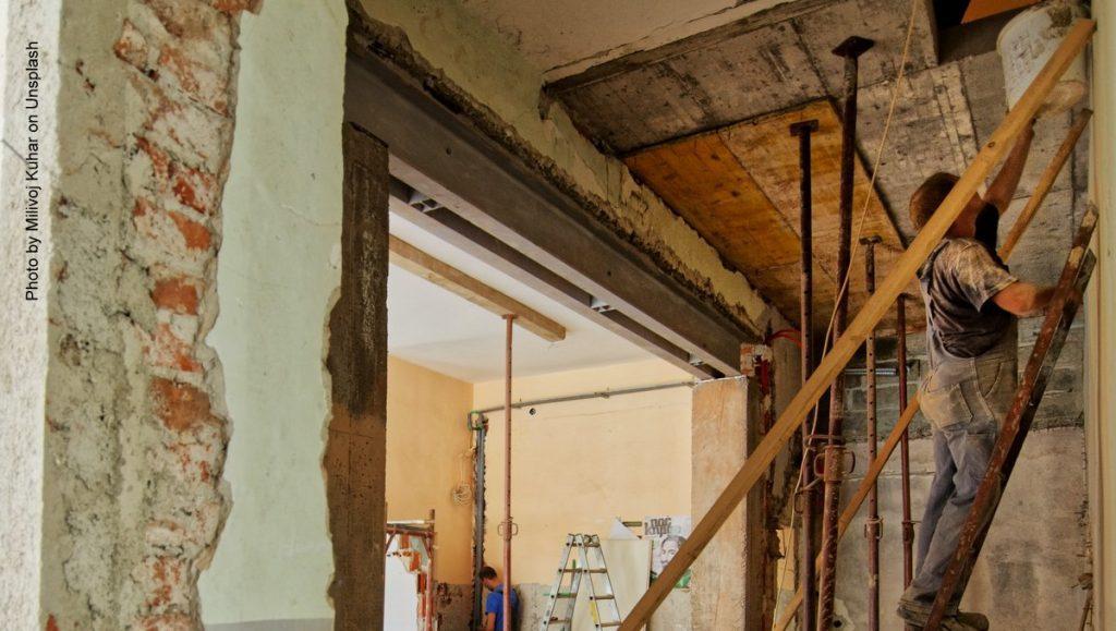 Mann auf einer Leiter renoviert