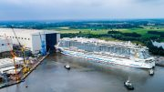 Luftaufnahme wie die AIDAcosma aus der Bauhalle der Meyer Werft schwimmt
