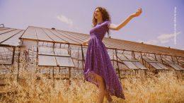 Frau im lila Kleid vor Gewächshaus