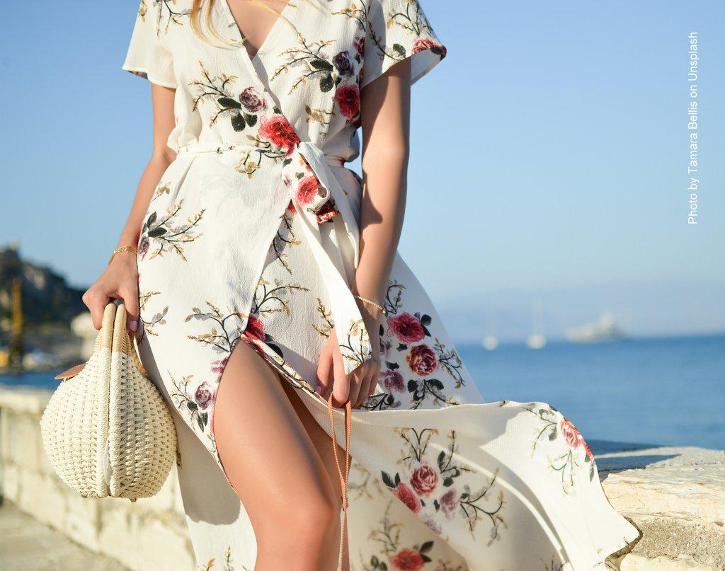 Frau mit Blumenkleid am Strand