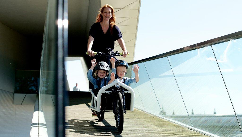 Lastenfbike Mutter mit zwei kleinen Kindern mit Helm