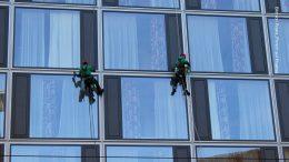Zwei Fensterputzer reinigen ein Hotel von aussen