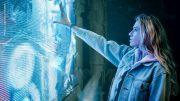 Junge Frau berührt eine leuchtende Bildwand