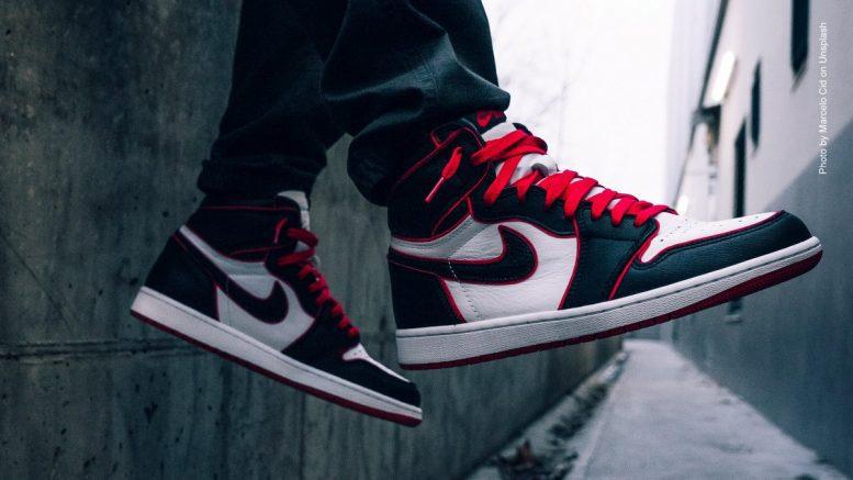 Mann sitzt auf einer Mauer, nur die Sneakers sind zu sehen