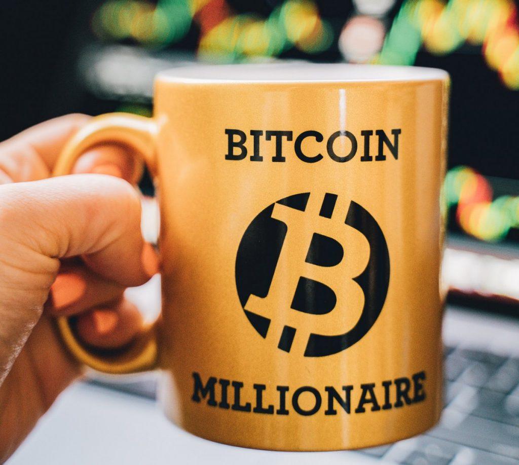 Gelber Kafferbecher mit Aufschrift Bitcoin Millionaire und Bitcoin Logo