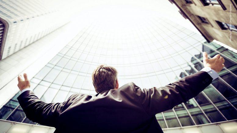 Mann freut sich über Geschäftserfolg zwischen Geschäftshausen mit Arme hoch