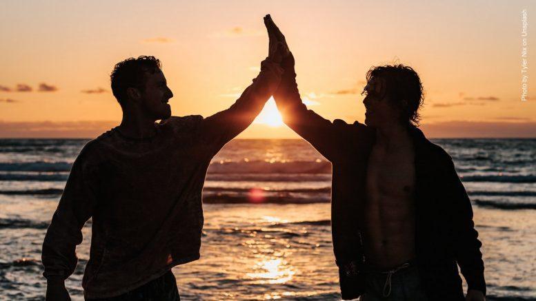 Zwei Männer vor einem Sonnenuntergang am Meer