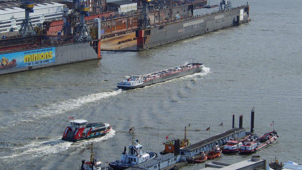 Blick auf die Elbe mit Hafenfähre, Schleppern am Kai und einem Binnenschiff