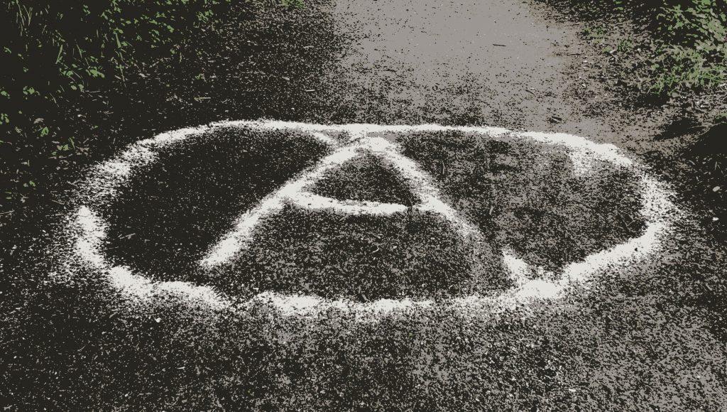 Zeichen in Form eines A mit Kreis auf einem Weg