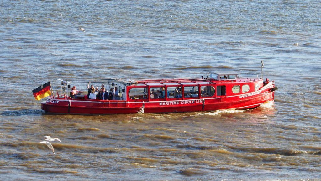 Rote Barkasse mit Fahrgästen auf der Elbe