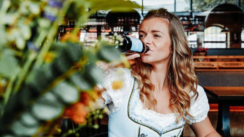 Frau im Dirndl trinkt Bier