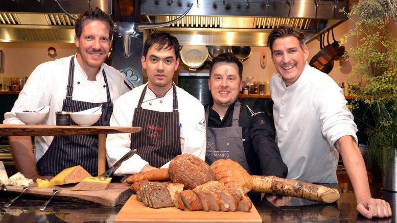 Vier Köche in der Gutsküche vor einem Brotkorb
