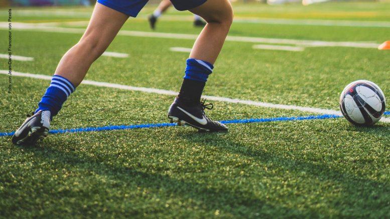 Frau spielt Fußball zusehen Fußballschuhe