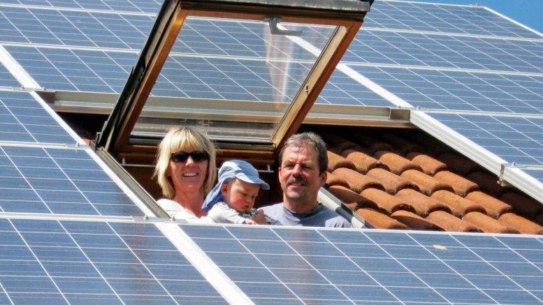 Familie schaut aus einem Dachfenster. Dach mit Solarstrommodulen