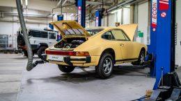 Ein gelber Vintage Porsche 911 in der Werkstatt