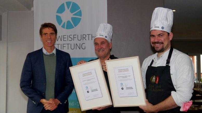 """Dr. Niels Kohlschütter, Vorstand der """"Schweisfurth Stiftung"""", zeichnet Jens Witt und Sebastian Junge mit der Tierschutz- Kochmütze"""